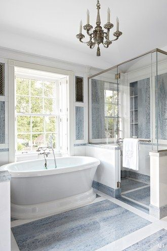 A bath in a Houston home conceived by architect Allan Greenberg and decorator Elissa Cullman features a chandelier from Remains Lighting, a Greenberg-designed shower, and a marble floor | archdigest.com