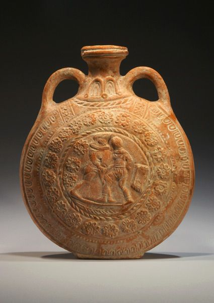 Roman molded redware moon flask with gladiators in combat in relief on both sides. Surronding the central image are bordering bands of roping, rosettes, and tongues; two arching handles on the soulder.  2nd-3rd Century AD