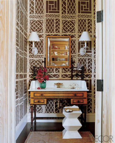 LYFORD TRELLIS WALLPAPER    The marble sink in the powder room of a home in Florida is set into an antique Victorian faux-bamboo dressing table, the ceramic seat is from Mecox Gardens, and the walls are papered in Lyford Trellis by China Seas.