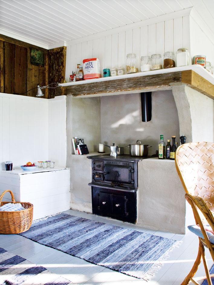 Köket på nedervåningen var nog det som tog mest kraft att renovera tillbaka till sitt ursprung. Halvvägs upp på väggarna och i taket sitter vitmålad pärlspont. Den gamla järnspisen är återställd i sitt ursprungliga skick och värmer nu både maten och huset. Och hela hörnet runt spisen har fräschats upp med vit puts. Alla hyllor har Michael satt ihop av enkla brädor på konsoler, från Ikea, som han målat vita.