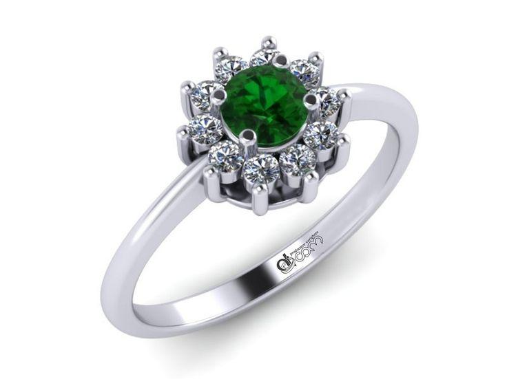 Acest inel din aur alb, cu pietre tintuite in forma petalelor unei flori care are, in chip de pistil, un minunat smarald de o frumusete rapitoare, constituie, in sine, cea mai inedita declaratie de dragoste si cerere in casatorie, cuvintele fiind de prisos.