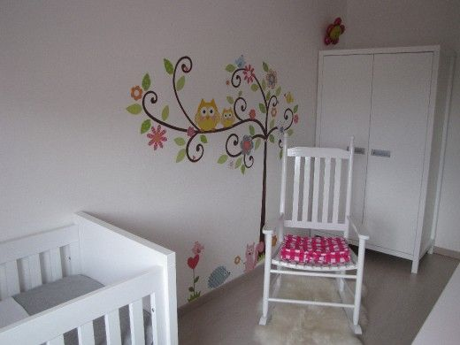 Lieve babykamer met een in het oog springende muursticker met schattige, gekleurde uiltjes. De kinderkamer heeft een zachte uitstraling door het rustige