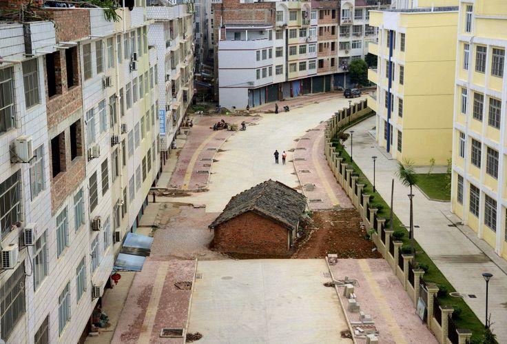 在南寧,因為賠償金問題,紅磚瓦建成的釘子戶與色彩鮮明的鋼筋水泥公寓,兩相應照下成為當地獨特的風景。Photo Credit: Reuters/達志影像
