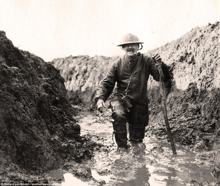 A soldier, pipe hanging from his mouth, uses a makeshift walking stick to propel himself through the knee-deep mud of the trenches