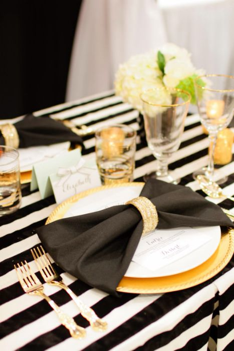 A napkin folded into bow looks stunning with a beautiful napkin ring. Source: Abby Mitchell Events. #napkinfold #tablescapes