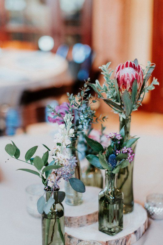 Boho wedding centerpiece idea - tree slice bases with delicate flowers in assorted vessels - protea and greenery {Copper & Birch}