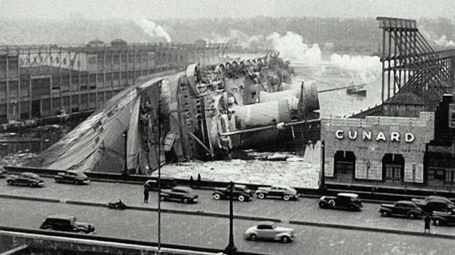 The ocean liner S.S. Normandie tips over on February 9, 1942 at New York City's Pier 88.