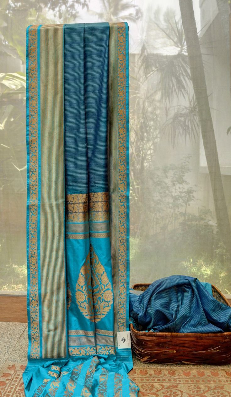 This striking aegean blue benares silk has textured stripes in atlas blue thread work. The border and pallu are in atlas blue with exquisite gold zari weaving. The blouse is also in atlas blue wove…