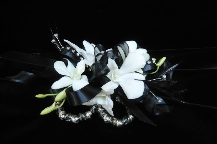 White dendrobium orchids on black satin ribbon with rhinestone accents on a black and silver bracelet  wrist #corsage for #prom by Emil J Nagengast Florist in Albany, NY.