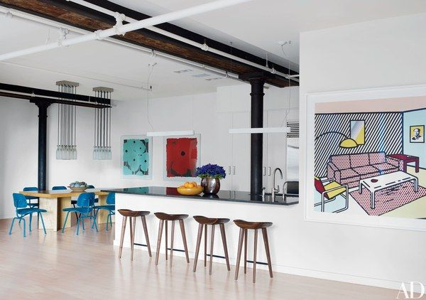 The open kitchen is equipped with a Sub-Zero refrigerator, Kallista sink fittings, and BassamFellows stools from Design Within Reach; at right is a Lichtenstein print. In the dining area, Tejo Remy light fixtures are suspended above a vintage Paul T. Frankl dining table; artisan Tanya Aguiñiga covered the Eames chairs with blue felt, and the flower images are by Donald Sultan.