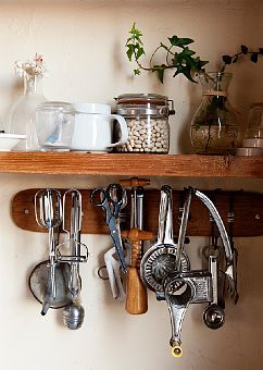 Vintage kitchen tools on a wood peg against a Swiss coffee wall.