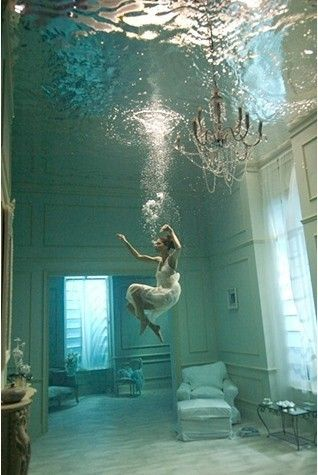 I bet it took them awhile to fill up that tank one, with water but the furniture they had to nail down. You can see the chair in the corner soaked and the cushions trying to release themselves to air. As well as the chandelier disturbed by her jumping in the water. Neat photo. I love it.