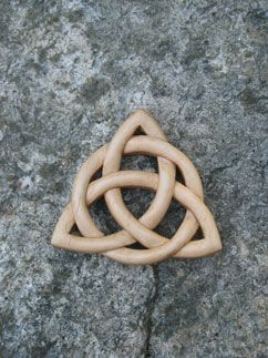 This is a traditional Celtic Knot uses the 'three loop' image of the Trinity with a circle woven into the triquetra to celebrate the 'oneness' of God. This knot is carved on both sides so that it can be hung in a window or opening. It is made of white birch. $75.00