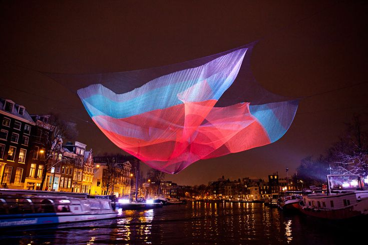 Janet Echelman's 230-foot-long aerial sculpture was installed over the Amstel River from atop the Amsterdam Stopera, which houses the City Hall and Muziektheater. Description from echelman.com. I searched for this on bing.com/images