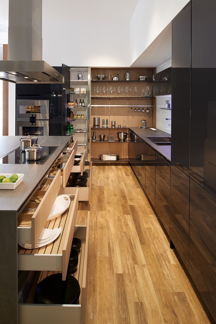 "SieMatic PURE, S2, lacquer, graphite grey gloss, nickel gloss integrated grip slot (cabinets/panels), Floating Spaces, wood veneer, titan oak matte (wall/shelf system), wall shelf with integrated task and LED atmospheric lighting Gaggenau: Combi-Steam Oven, Oven, Warming Drawer, 18"" Fully-Integrated Freezer Column, 24"" Fully-Integrated Refrigerator Column, Full-Surface Induction Cooktop, Island Hood, stainless steel Dornbracht: Lot mixer, water dispenser and hand spray, polished chrome"