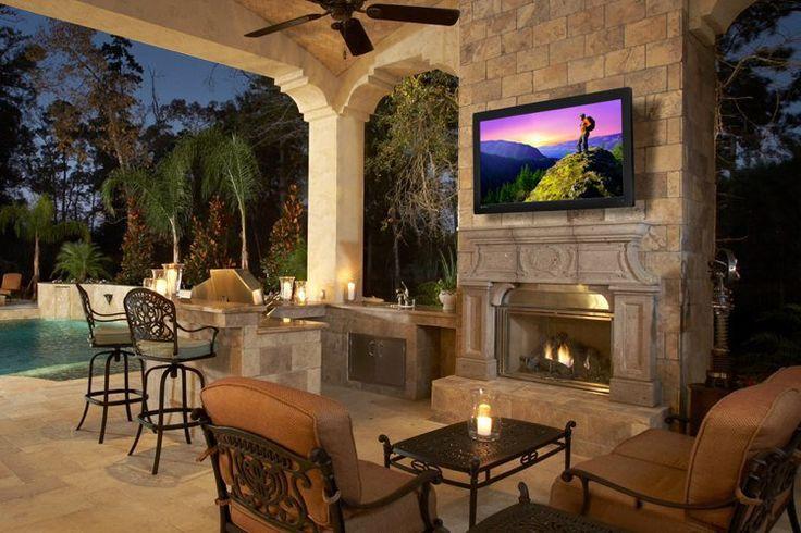 terrasse couverte et carrelée aménagée avec une cuisine, barbecue extérieur et cheminée