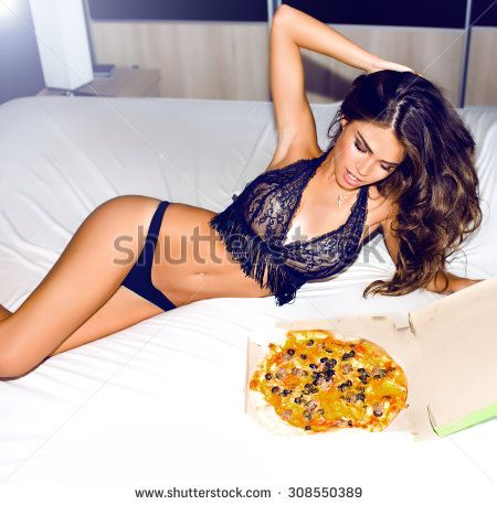 Outdoor Sexy Brunette woman holding tasty pizza with cheese.Woman order at home delivery and waiting for her friends,home party,pajama party,weekends,laughing,lifestyle portrait,no diet,hungry girl