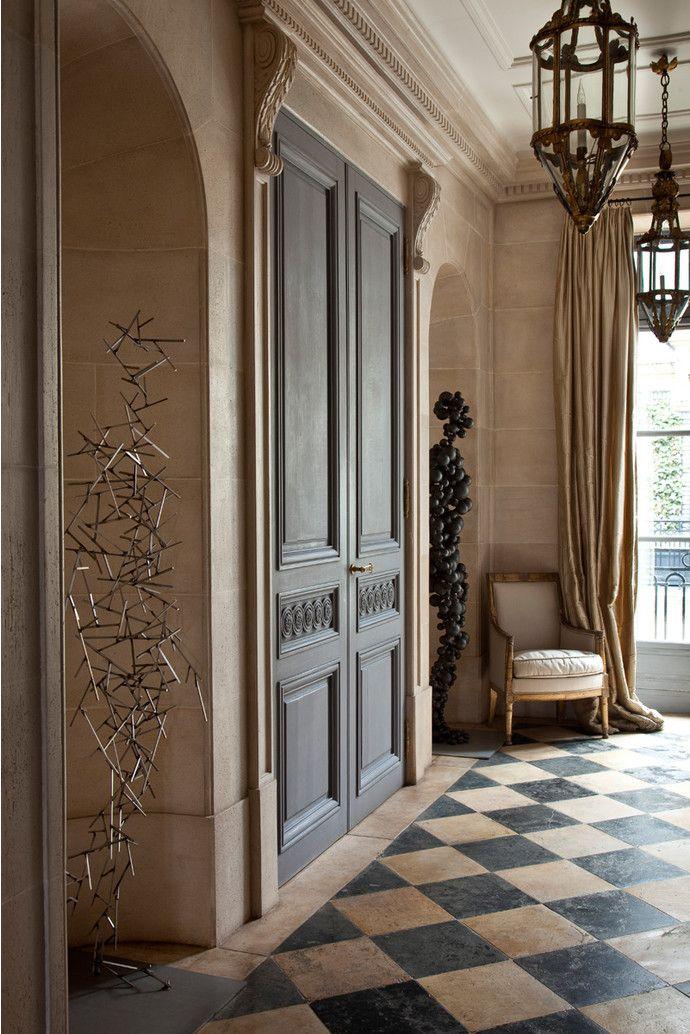 Холл квартиры. В нишах — скульптуры Энтони Гормли. В углу у окна кресло эпохи Директории. Вместо ламп используются итальянские фонари XVIII века, к которым подведена элект- ропроводка.