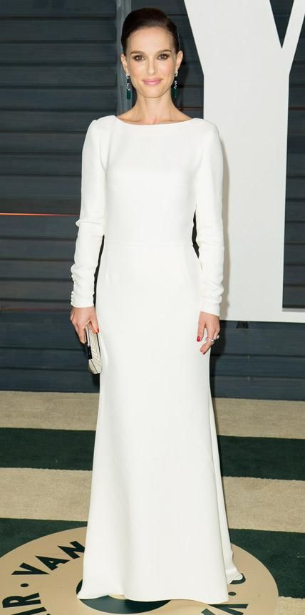 Natalie Portman epitomized elegance at the Vanity Fair Oscars party in a minimalist white long-sleeve heavy silk gown, adding subtle touches of shine with drop earrings and a metallic clutch.
