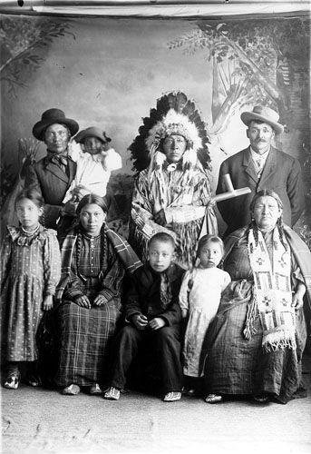 Shoots Holy (with feathered headdress) and Wise Spirit (with beaded breastplate) and their family - Hunkpapa - circa 1900