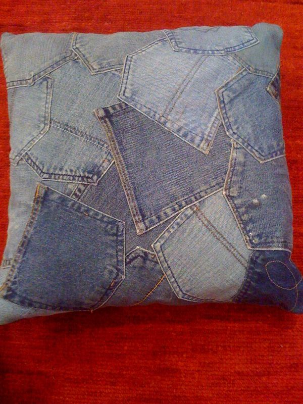 Loloi patchwork denim pillow as detail from rugs made from recycled blue jeans.    Loloi takes recycled blue jeans, puts them together as a patchwork, makes a rug the same way the artists of Gee Bend did with their quilts