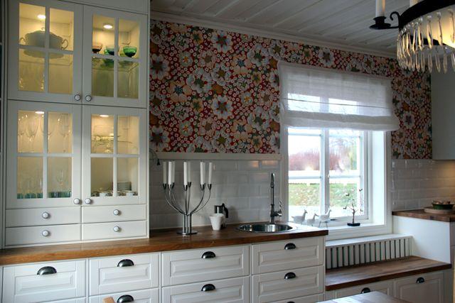 Bänk framför fönstret, vitt fasat kakel, snyggt tak, vita skåp och Josef Franks Eldblomma på väggarna.