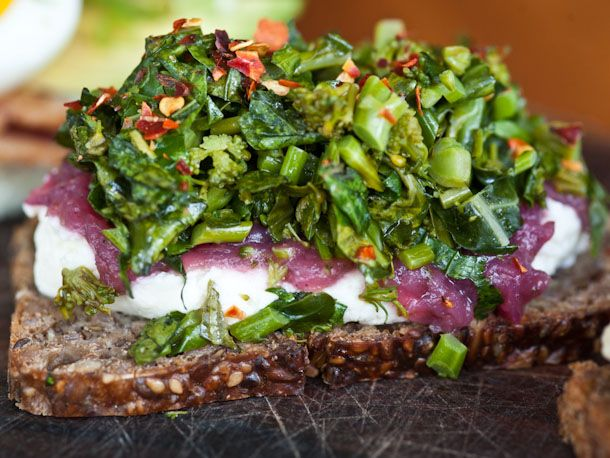 This smørrebrod is topped with housemade goat cheese and a beet-tinted onion jam, along with spicy broccoli.
