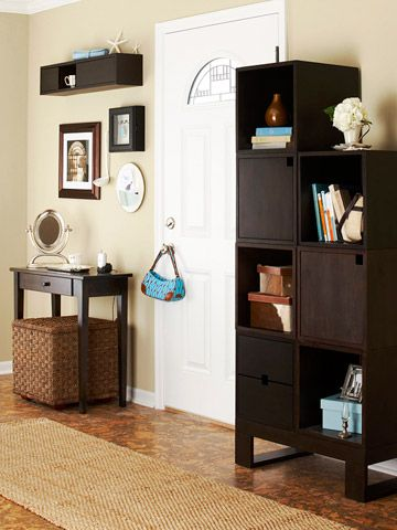 """Use Entry Wall Space Wisely: Wall space on each side of the door keeps this entry attractive and orderly. The tall stair-stepped cabinet lends style to the area with both open and closed cubes for display as well as concealed storage. A lidded basket under the table on the opposite side provides a place for shoes and outerwear. Above the table, a shadowbox houses keys and a repurposed ladle gathers loose change."""