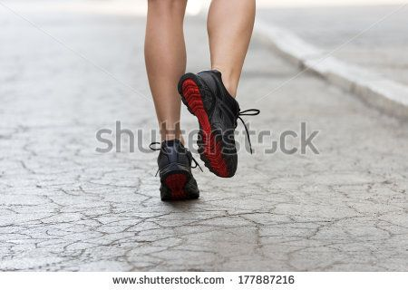 back shot of young lady with fitness shoes running on cracked road . USED SHOES - stock photo