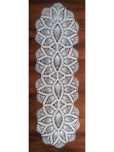 """Add a bit of elegance to your table with this exquisite table runner! Design requires 500 yds of size 10 crochet cotton and a size 7 steel crochet hook. Size: 38""""L x 12""""W."""