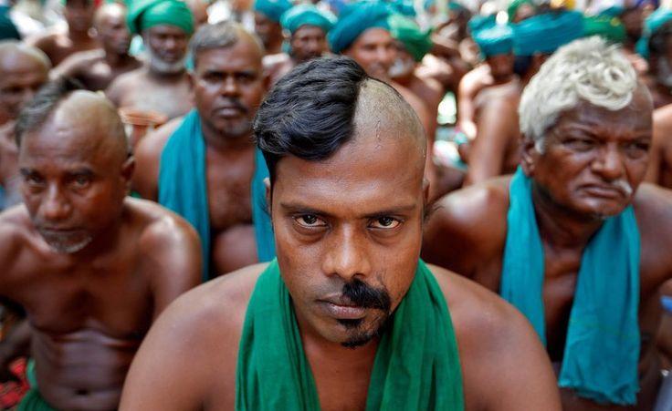 A Nuova Delhi, in India, gli agricoltori dello Stato meridionale del Tamil Nadu siedono con le teste mezze rasate per protestare contro il governo federale.