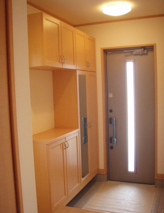 Typical genkan, or entryway, in an apartment. Shoes can be stored in the cabinets.