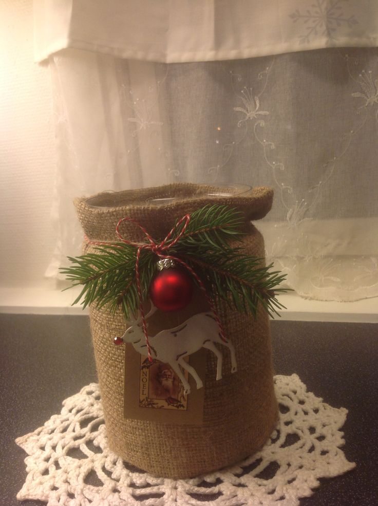 Glass vase, decorated with somre fabric and  x-mas decor, and then you have something rustic for flowers, or ornaments. Used as a centerpiece