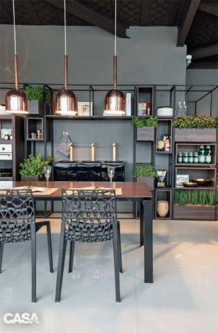 ESTANTE DE IMPACTO Tudo fica à mão e à vista nesta cozinha assinada pelos arquitetos Marcos de Paula e Luciana Savassi. Desenhada pala dupla, a estrela do ambiente é a estante de estrutura metálica, que acomoda caixas de madeira para cultivo de orgânicos. Cadeiras da Flexform.