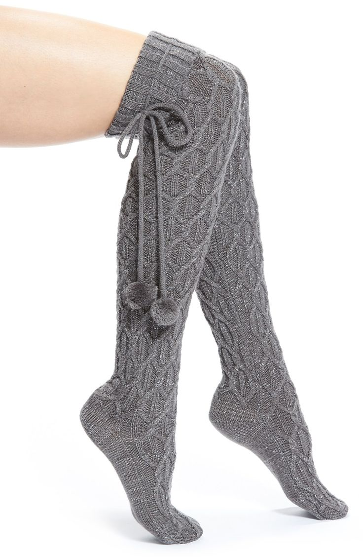 Sparkly threads intertwine with cozy cable-knit patterns on these stylish over-the-knee socks finished with festive pompom-tipped ties. These UGG Australia socks are perfect when lounging at home.