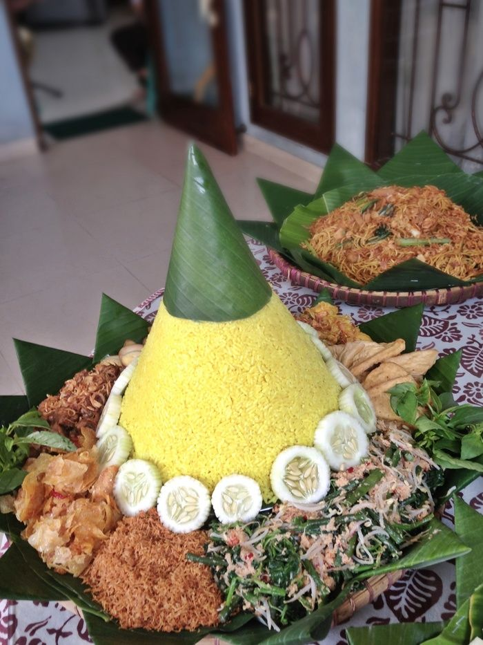 Nasi tumpeng - On several special events, nasi kuning is shaped into a yellow cone popularly known as nasi tumpeng, served on a tampah with an assortment of side dishes. (Photo by Adisti Chandra)