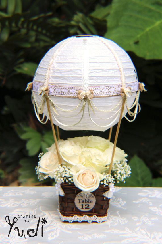 This beautifully handcrafted Hot Air Balloon centerpiece is made using a white paper lantern that has been adorned with high quality gold ribbons,