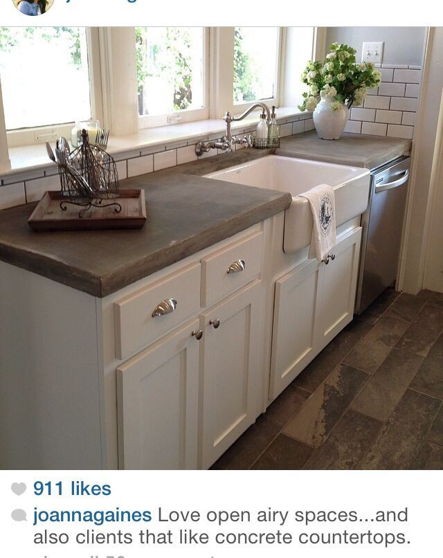 Concrete counter tops add a nice touch to this farmhouse style kitchen