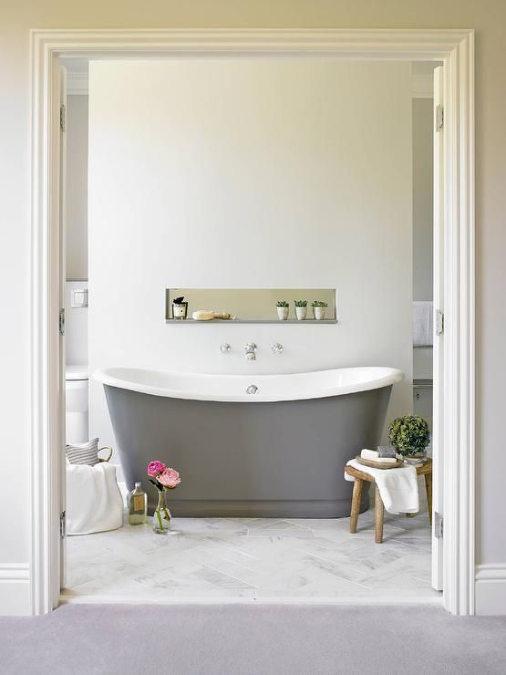 A bathroom wall partition is fitted with a gray quartz ledge accented with a row of cacti lined a freestanding gray bathtub, The Cast Iron Bath Company Newminster Tub, placed atop a marble herringbone floor.