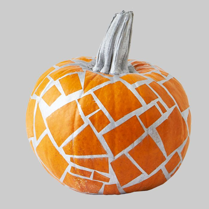 Not into pumpkin carving this year? Create a mosaic pumpkin using painter's tape and spray paint.