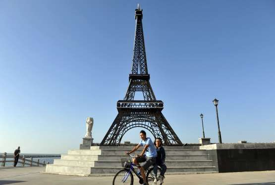 CHINA'S KNOCK-OFF LANDMARKS:  Residents ride a bicycle past a replica of the Eiffel Tower built next to a residential complex in Yantai- REUTERS/Stringer