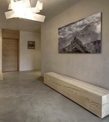 Wooden bench, glass light fixture, cement walls and floors