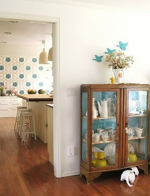 Love the blue details .. wallpaper & birds, and painted back of display case.