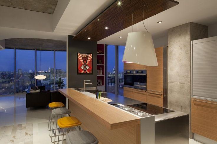 cuisine moderne avec hotte îlot blanche, armoires et bar petit déjeuner en bois et spots led