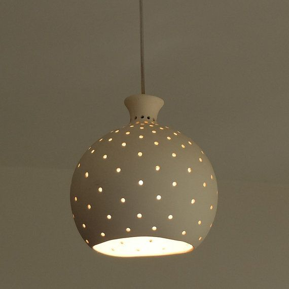 A Hanging Light Fixture Made Of White Clay And Delicately Perforated The Lamp Is Attached