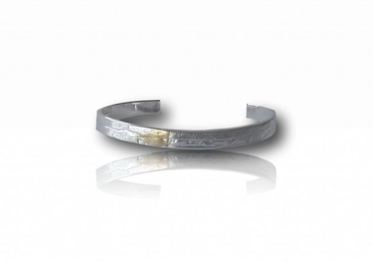 Silver and gold textured bangle, Gavin MacSporran, 2016. The interpretation of the raw elegance and beauty of the Australian landscape, the interaction of water, fire and earth distilled through the hammer is his passion. Represented by Henry Jones Design Gallery