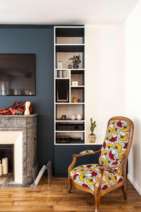 Dans un coin du salon, une chaise Voltaire a été tapissée d'un tissu Wax