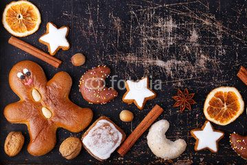Ginger bread man, christmas cookies and spices on old dark scratched baking sheet