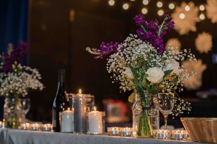 Doing flowers yourself saves a ton.  baby's breath, stock flowers and white roses in ball jars.  ikea candles too.  #DIYwedding #Weddingcandles #DIYflowers #weddingflowers #babysbreath