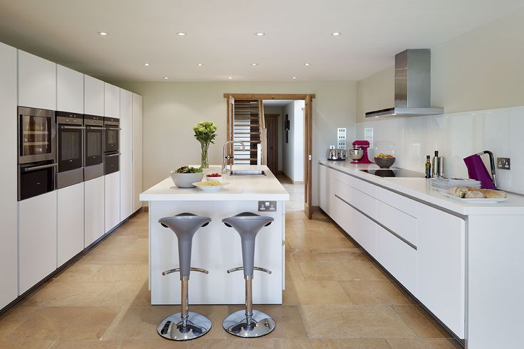 Island end stools provide an ideal social space to converse with the cook or have a bite to eat. Corian worktops provide hard wearing and easy to maintain surfaces. #kitchens #b1 #bulthaup